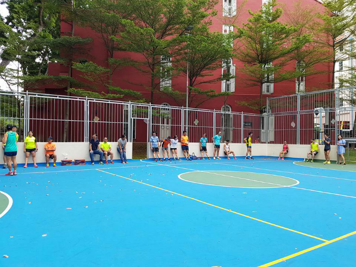 Runners line the sides of an outdoor basketball court after the drills session. [Photo courtesy of Chin CK]