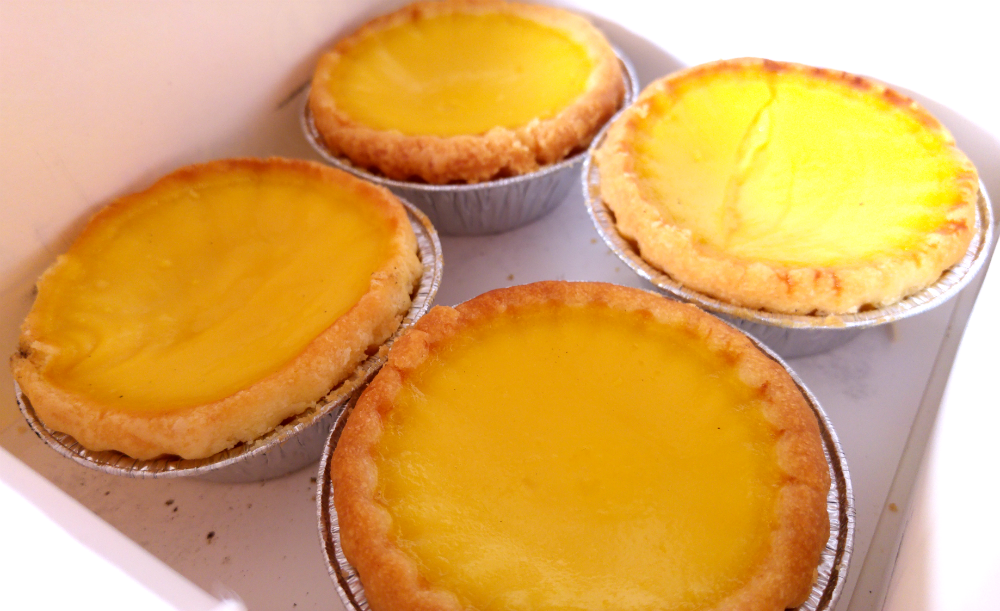 Savouring the egg tarts in all of their eggy goodness.