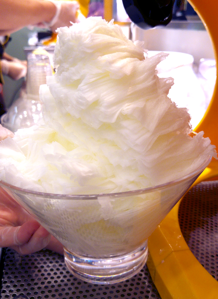 A snowflake ice dessert is being prepared for serving.