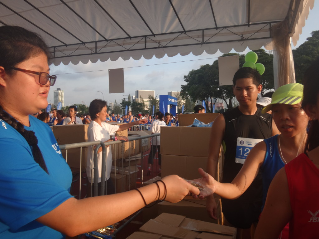 A volunteer passes a runner her medal.