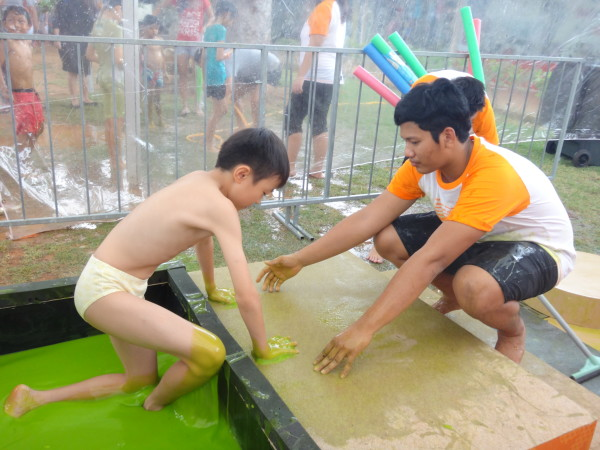 A kid gets helped out of a pool of slime.