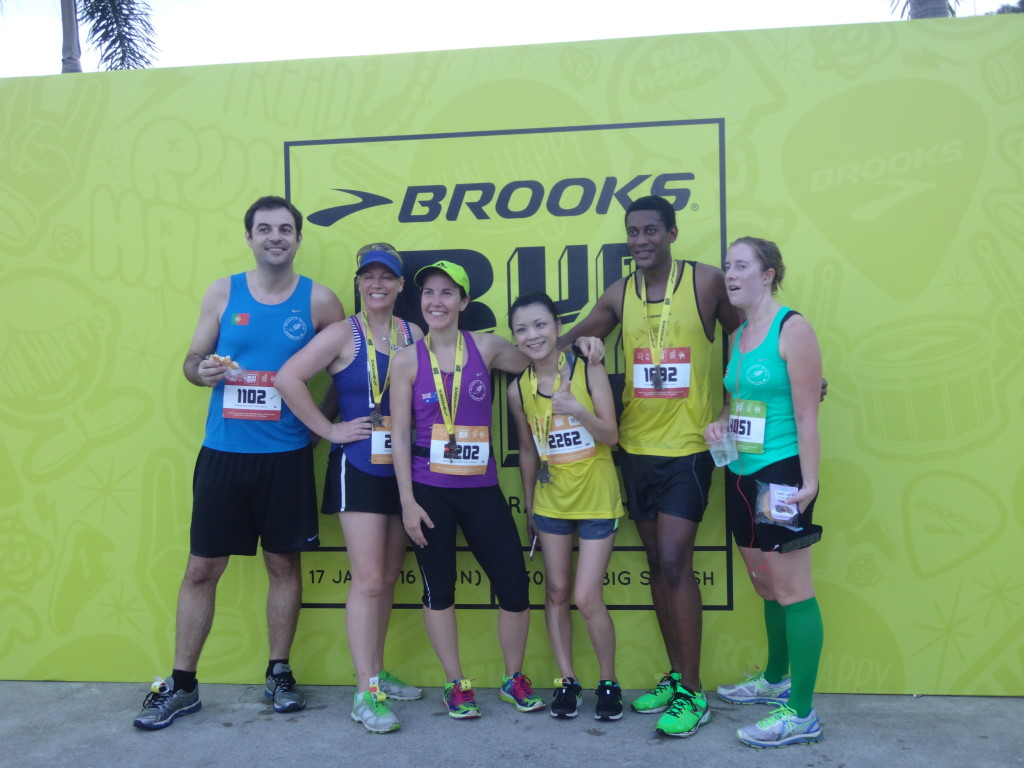Runners take a photo at the Brooks signage for keepsake.