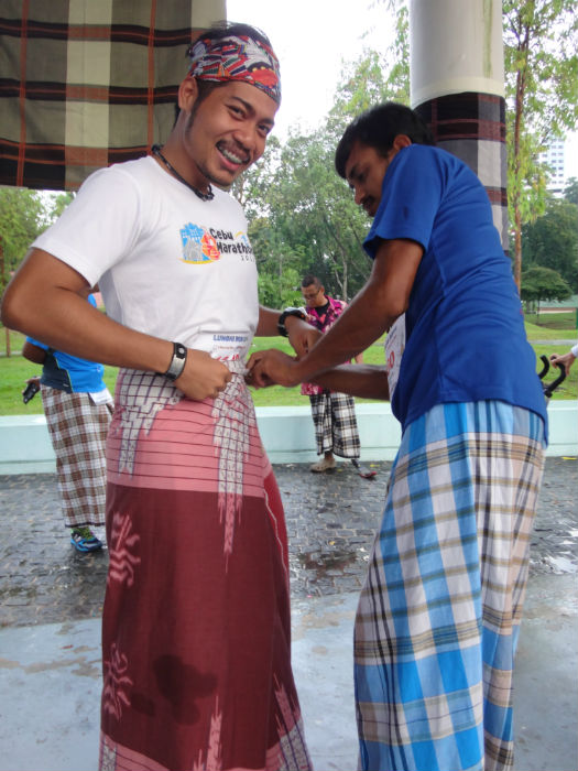 Runners help each other to put on the sarong before the race.