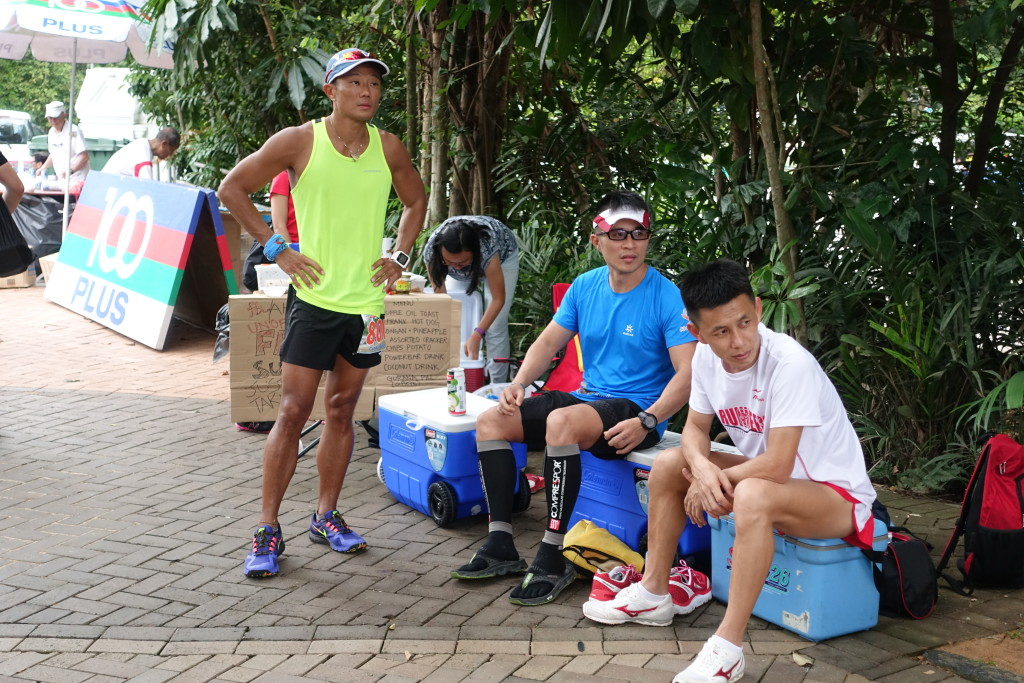 A runner takes a breather with two supporters looking on.