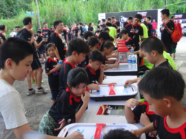 Children engaging in a game of Air Hockey at the race village.