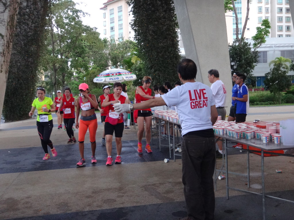A runner accepts a drink from a hydration station during the race.
