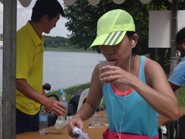 A thirsty runner hydrates herself.
