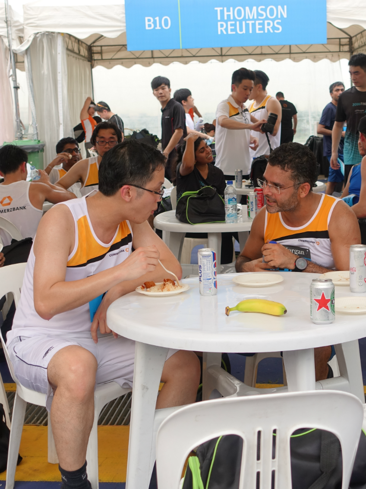 Runners mingling with their colleagues at a corporate tent.
