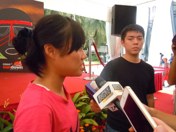 Mok Ying Rong (in pink) gets interviewed by the media.