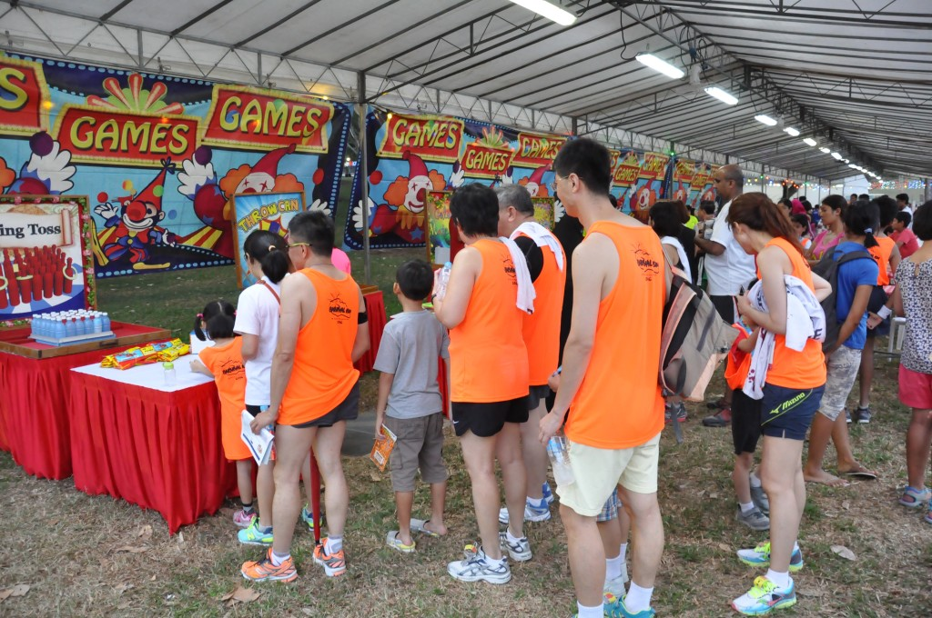 Runners queue up to play carnival games.