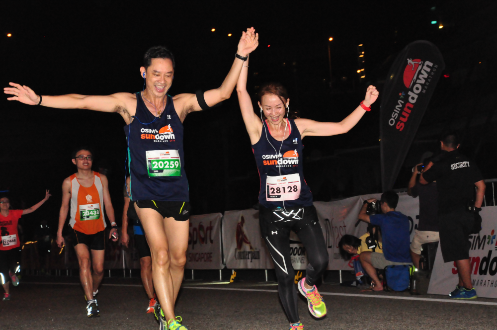 Runners hold hands across the finish line.