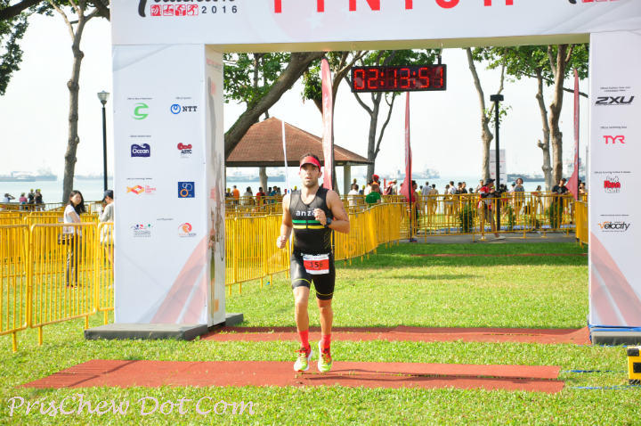 A triathlete crosses the finishing line.