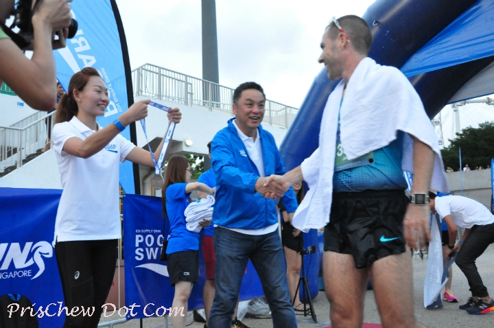 A winner is presented his finisher's medal by Neo Jie Shi, Pocari Sweat Singapore ambassador and Rio-bound marathoner.