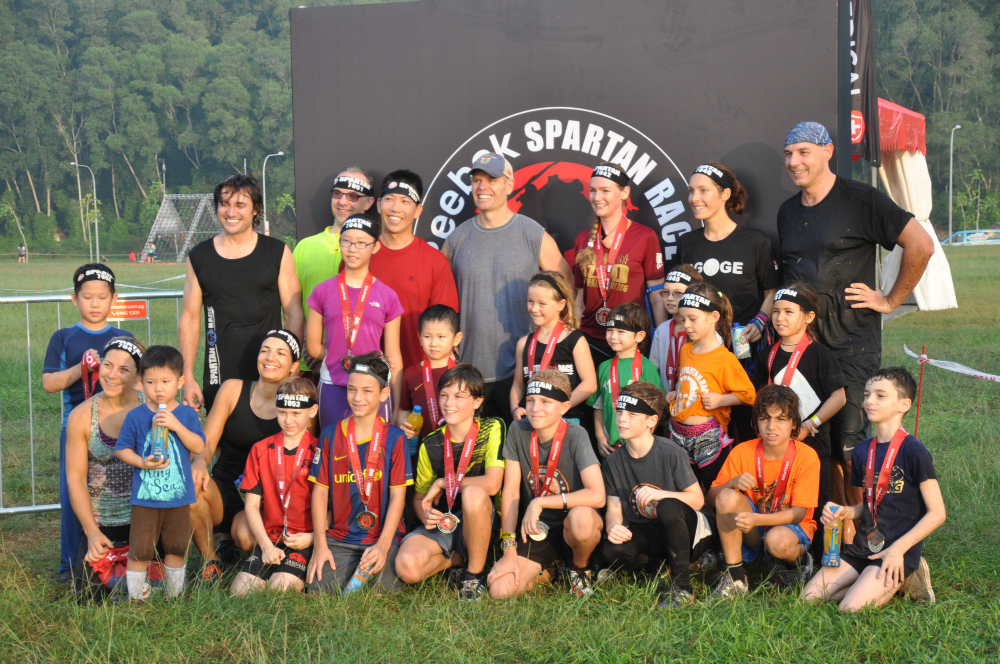 Happy Spartan Race finishers pose with their medals.
