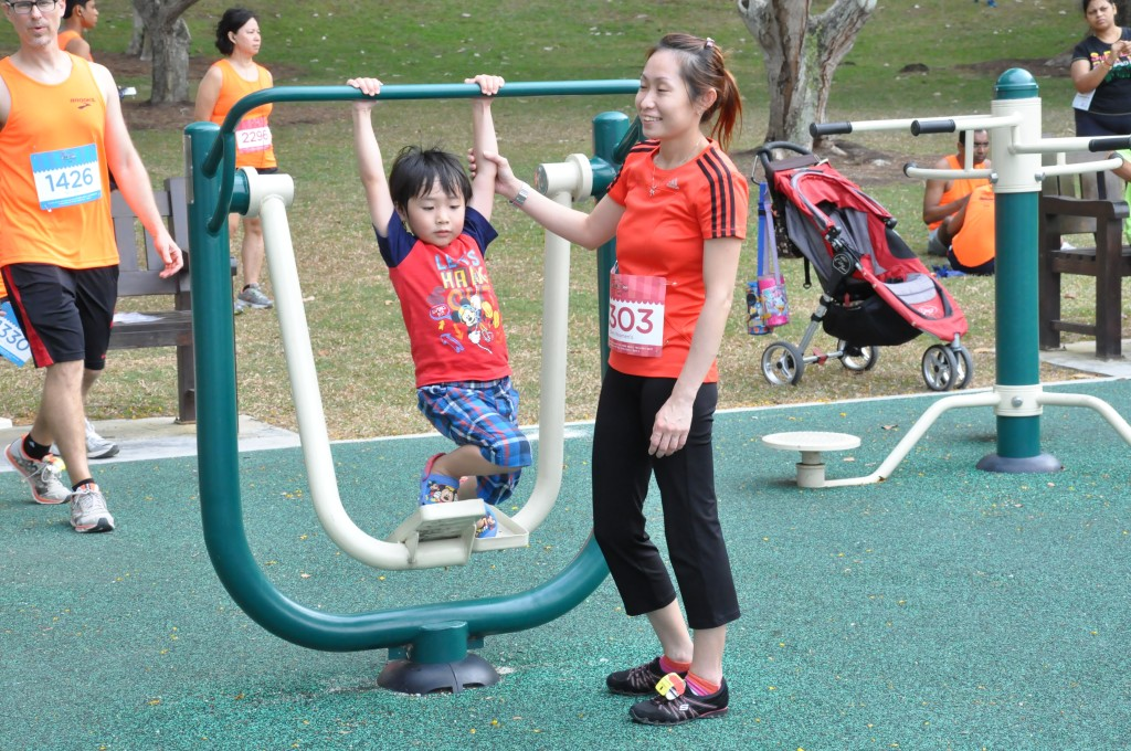 A runner and her young child enjoy the playground at Bedok Reservoir.
