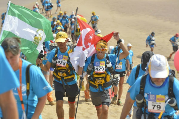 Wei Chong and Ian carrying the Singapore flag during the Charity Stage of the MdS.