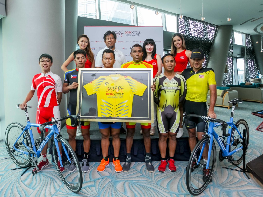 Team Singapore Cyclist, Low Ji Wen (extreme left), along with Team Captains Jerry Jr. Aquino from Philippines (second from bottom left), Yoeun Phyuth from Cambodia (third from bottom left), Jeevan Manjula Jayasinge Silva from Sri Lanka (third from bottom right), Reduan Bin Yusop from Brunei (second from bottom right), Muhammad Fauzan Bin Ahmad Lutfi from Malaysia (extreme bottom) right, Mr Suhaimi Haji Said, President of Singapore Cycling Federation (second from top left), Ms Koh Ching Ching, Head of Group Corporate Communications OCBC Bank (second from right), and the two OCBC Sportive girls pose for a group photo at the official OCBC Cycle 2015 press conference that was held at Hotel Jen, Orchardgateway Singapore on Friday afternoon. (Photo Credit: OCBC Cycle 2015)