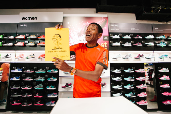 Haile Gebreselassie and his signed caricature (Credit: adidas).