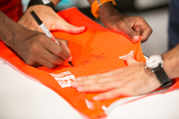 Haile signs the SCMS Supernova Short Sleeve Tee. (Credit: adidas)