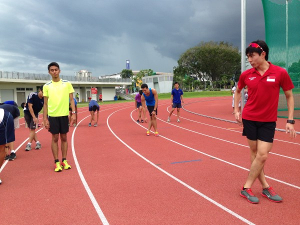 Soh (right) is observing as runners do warm-up exercises at a training clinic.