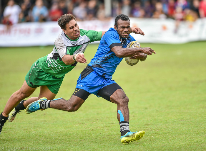 Daveta's Jerry Tuwai darts past a player from Sunnybank during the Pool A match at the Singapore Cricket Club International Rugby Sevens. (Photo Credit: SCC 7s).