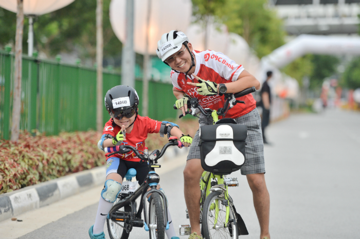 A kid and parent posing for the camera in the midst of completing their 20-minute ride at OCBC Cycle 2016 at Singapore Sports Hub. (Photo Credit: OCBC Cycle)