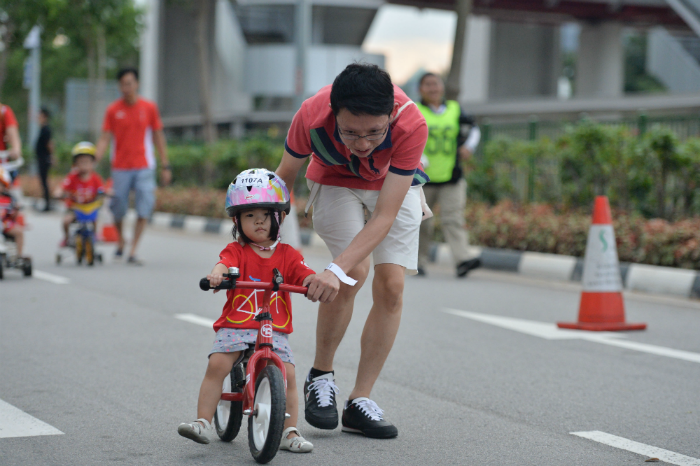 A parent assisting his daughter during the Mighty Savers® Kids and Family Ride (2 to 3-years-old) at OCBC Cycle 2016 at Singapore Sports Hub. (Photo Credit: OCBC Cycle)