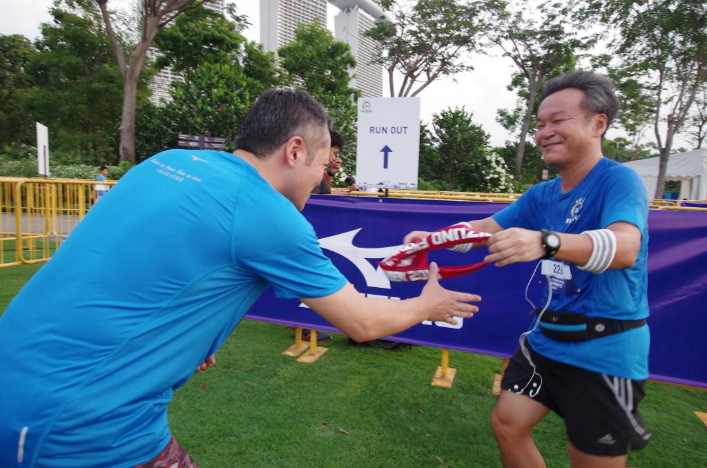 A runner hands the sash to his team-mate. Credit: Mizuno Ekiden 2015