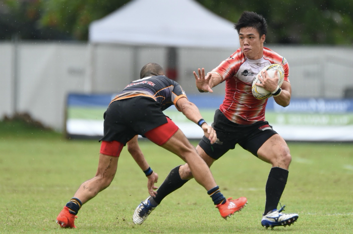 Singapore National Team vice-captain, Nicholas Yau attempts to hold off a tackle in the closely fought Pool C match between the Singapore National Team and the Tamariva Rugby Football Club at the Singapore Cricket Club International Rugby Sevens. (Photo Credit: SCC 7s)