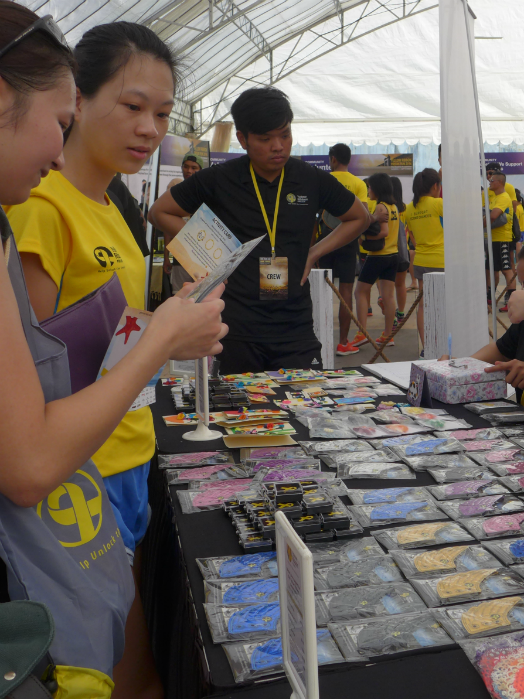 Runners look at one of the merchandise booths at the race village.