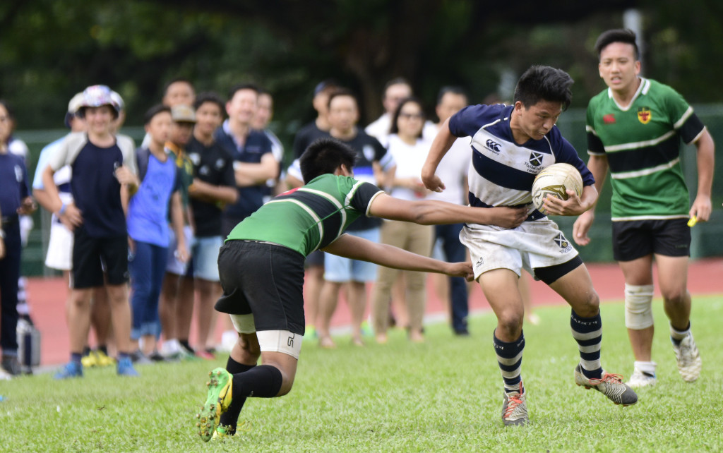 Supporters anxiously looking on as a player from Raffles Institution (left) attempts to tackle his opponent from Saint Andrews (right). (Photo Credit: Eric Lim/ Singapore Cricket Club)