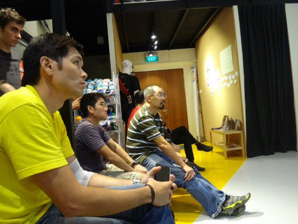 The audience is listening intently to Adrian Mok.
