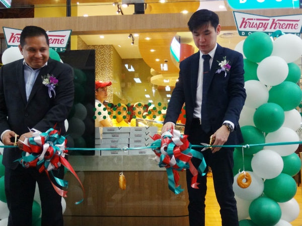 Krispy Kreme Director, Adrian Tan  (Right) cuts the ribbon to declare the store officially open.