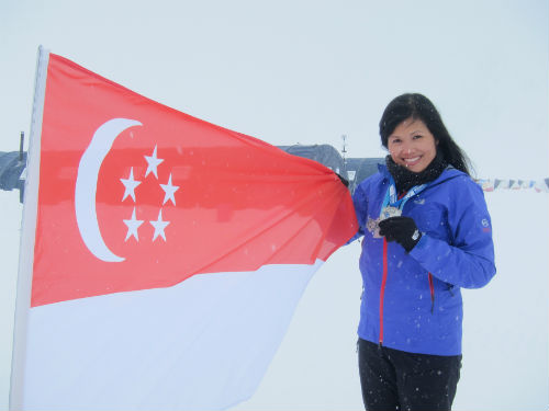 Yvonne flies the Singapore flag high in Antarctica. (Courtesy of Yvonne Chee).