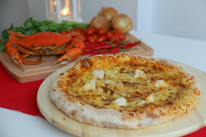 The pizza is served with crab meat chunks, onions and cherry tomatoes.