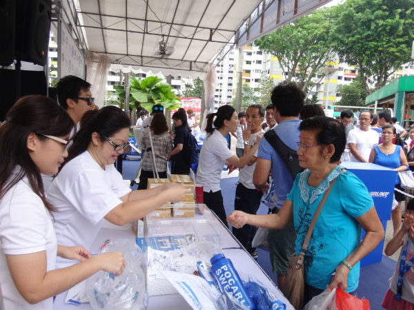 A fan collects her prize from the Pocari Sweat organisers.