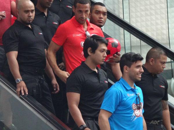 Rio Ferdinand and Sergio Aguero come down the escalator.