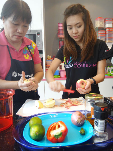 Chef Flossie Lio demonstrates to a participant how to peel apples for the Apple Salsa.
