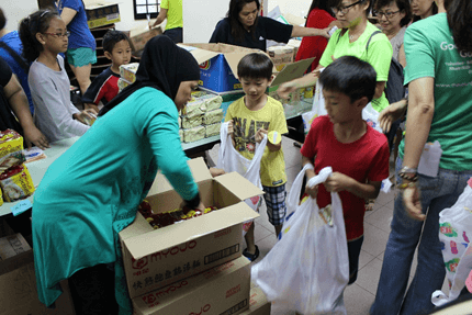 Young children helping to pack goodie bags for VSB's pre-CNY distribution. (Credit: VSB & SKM).