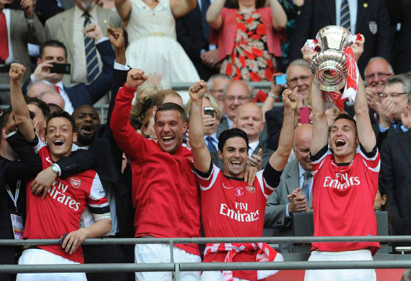 Vermaelen holds aloft the FA Cup trophy. (Image from arsenal.com)
