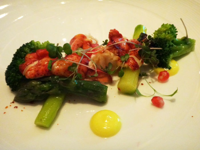 Maine Lobster prepared with asparagus, broccoli, fresh pomegranate and tarragon dressing.