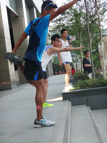 Marcus demonstrating a stretching exercise to runners at the NTUC Income Run 350 clinic.