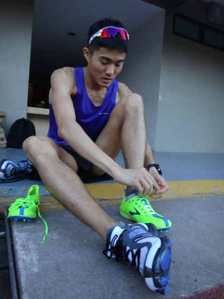 Mok Ying Ren laces up his shoes before a run.