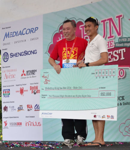 Mok Ying Ren, winner of the MediaCorp Hong Bao Run, posing with his victory cheque.