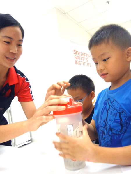 An SSI dietician (left) educates a young participant about sports drinks.