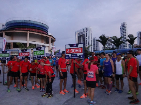 The pacers in their bright red and pink tees, holding their prominent signboards.