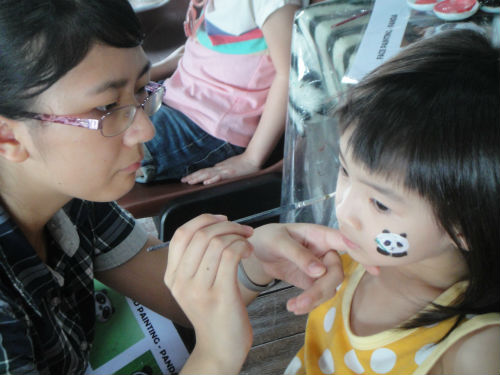 A girl gets a panda painted on her face.