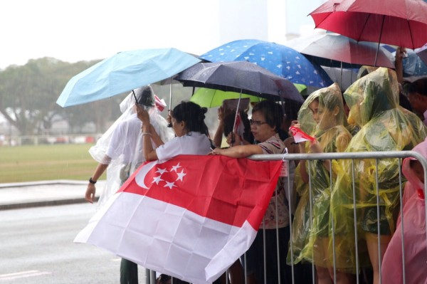 Singaporeans brave the rain while waiting for the funeral cortege to pass by.  Photo: singapore.coconuts.co