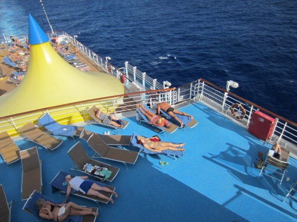 People are sunbathing on the cruise ship's upper deck.
