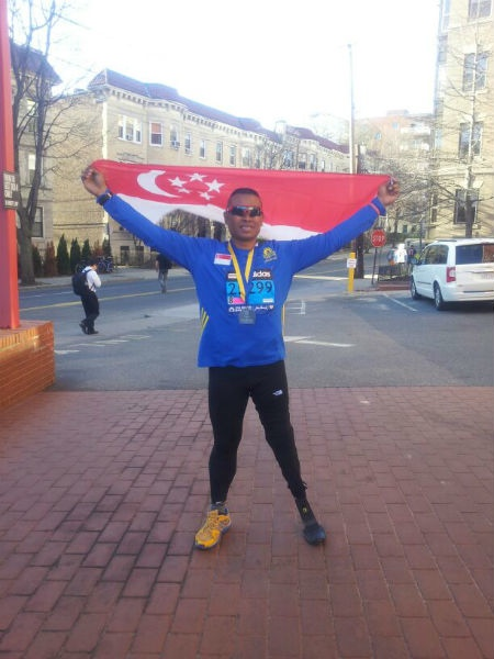 Singapore Blade Runner, Shariff Abdullah, holds the Singapore Flag high and proud at Boston.